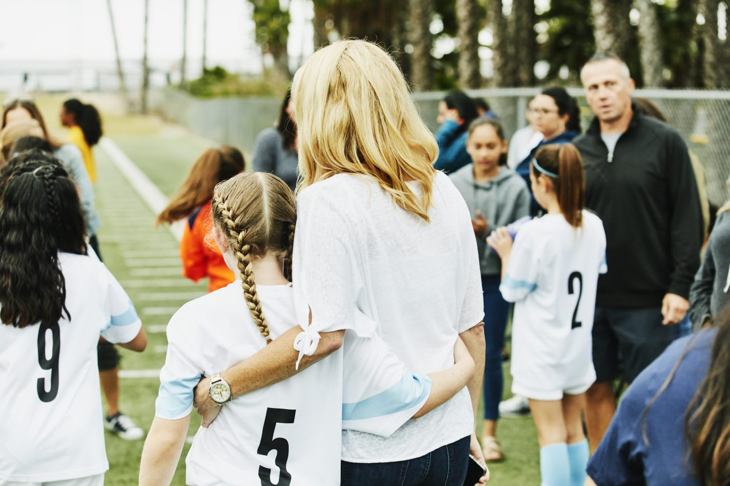 Mother embracing young female soccer player on sidelines after game. Purpose, purpose driven life, joy, GamePlanA.