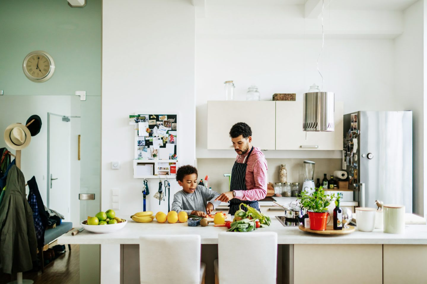 A father and son at home in the kitchen helping each other prepare some lunch.