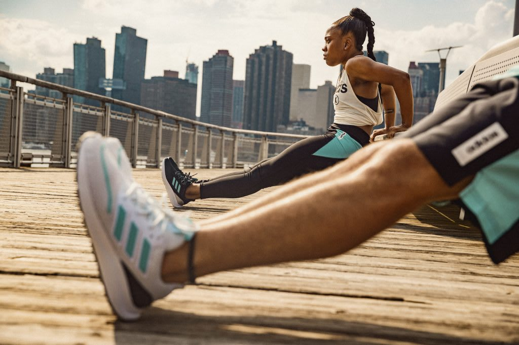 A women and a man stretching on a bridge in front of a city skyline. Mindset, Athlete, Exos, Positive Mindset, GemePlanA.
