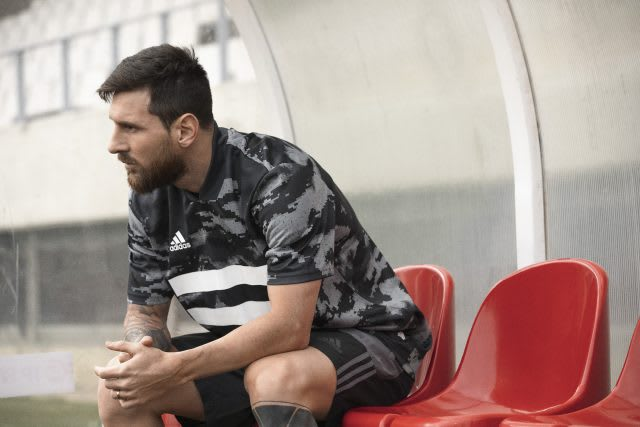 Football Star Lionel Messi sitting on a red substitions' bank.