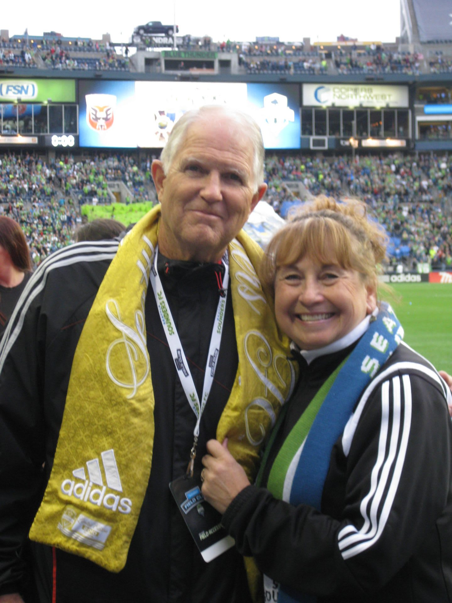 Elderly couple smiling at soccer game wearing adidas product, football, fans, game, sports, spectator
