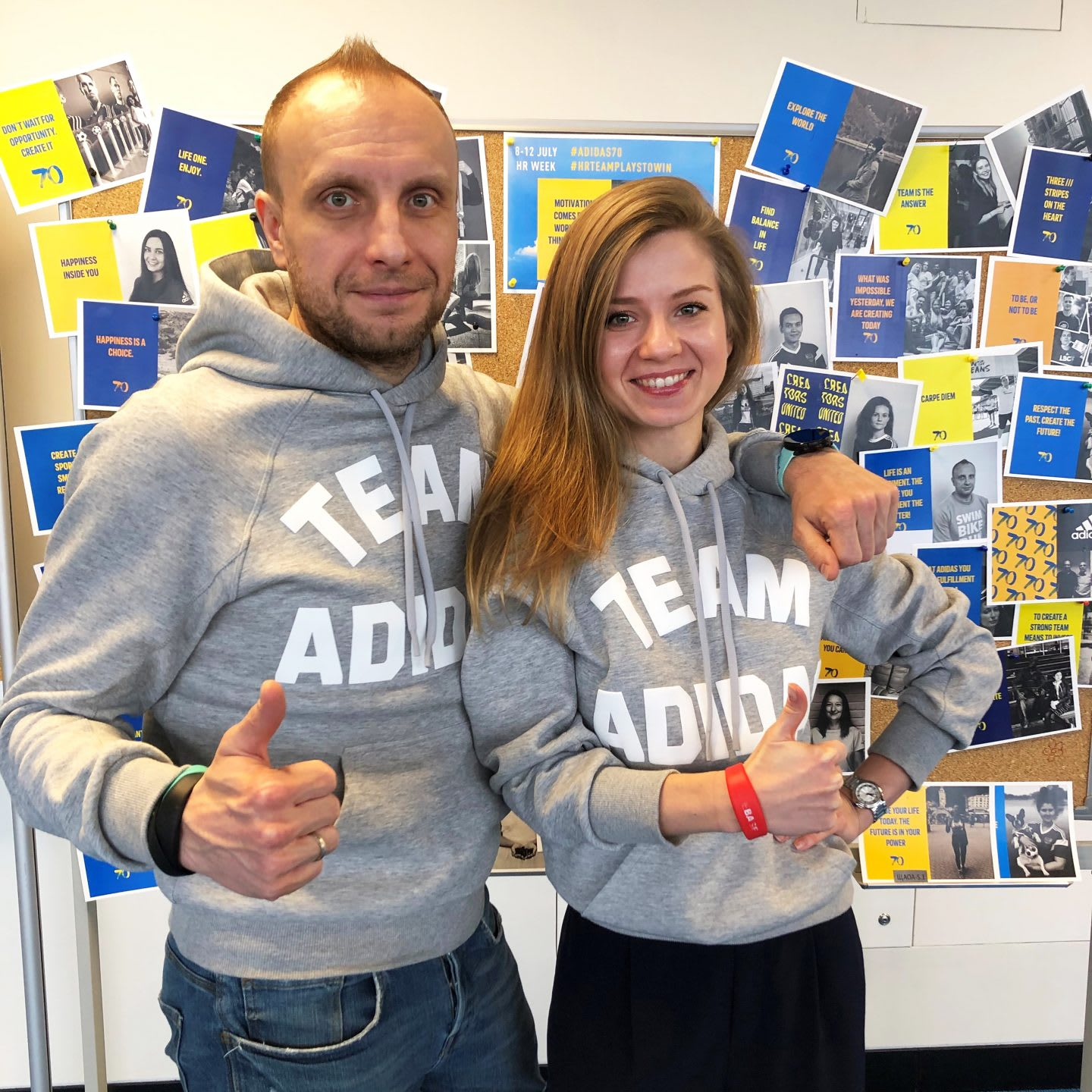 Man and woman wearing grey sweatshirts smiling with thumbs up gesture, teamwork, team, collaboration, happiness, workplace, worklife, culture, adidas