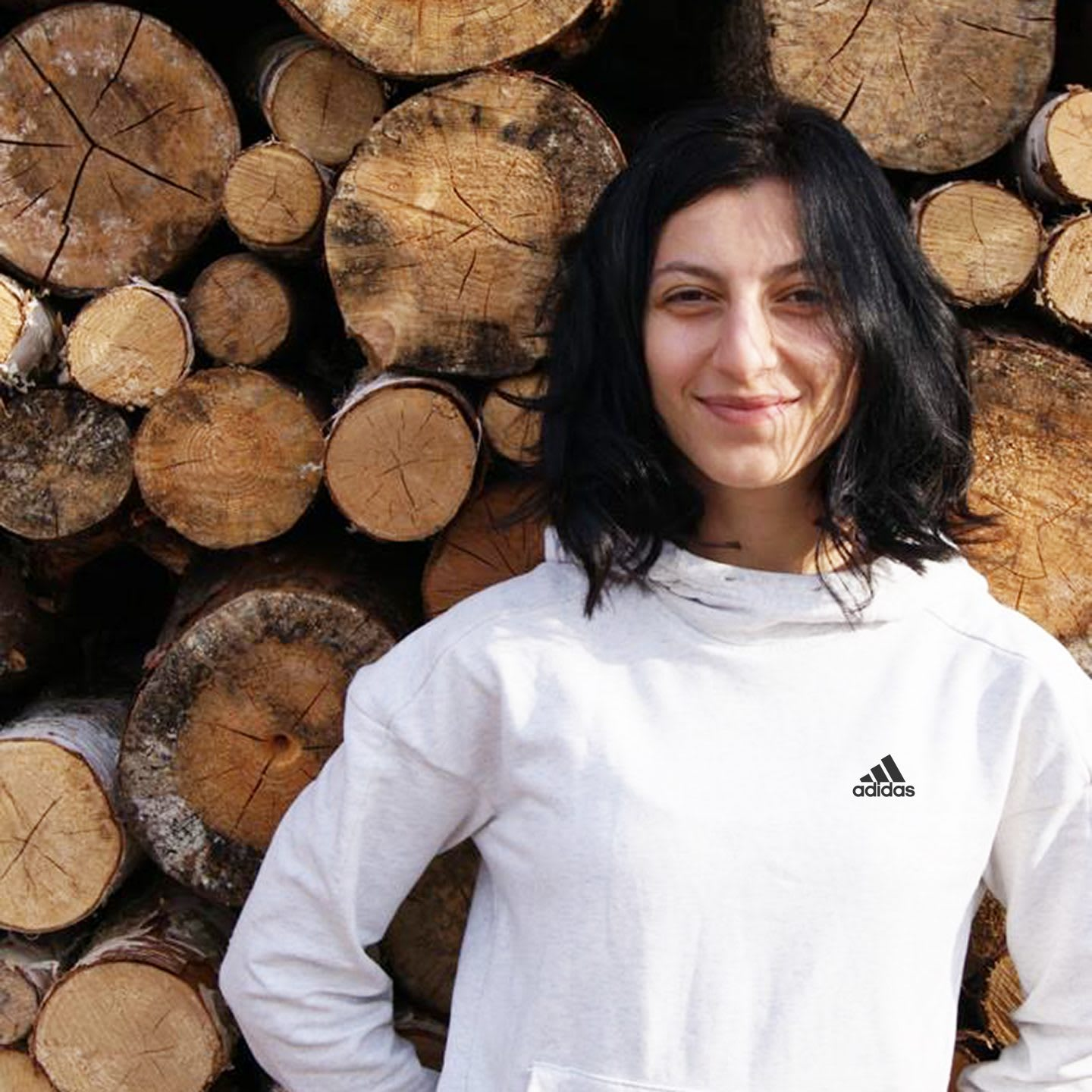 Woman with dark hair wearing adidas sports clothes smiling in front of logs, woman, girl, employee, adidas, sports