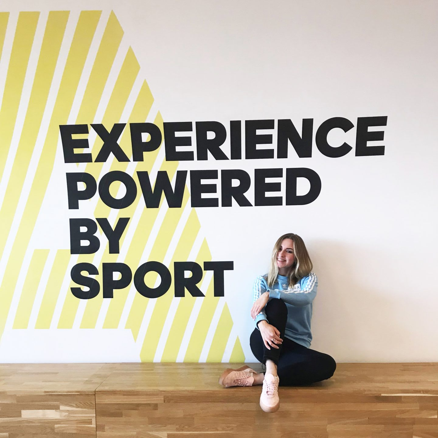 Woman sitting in front of a sign on the wall, adidas, employee, office, culture, sport