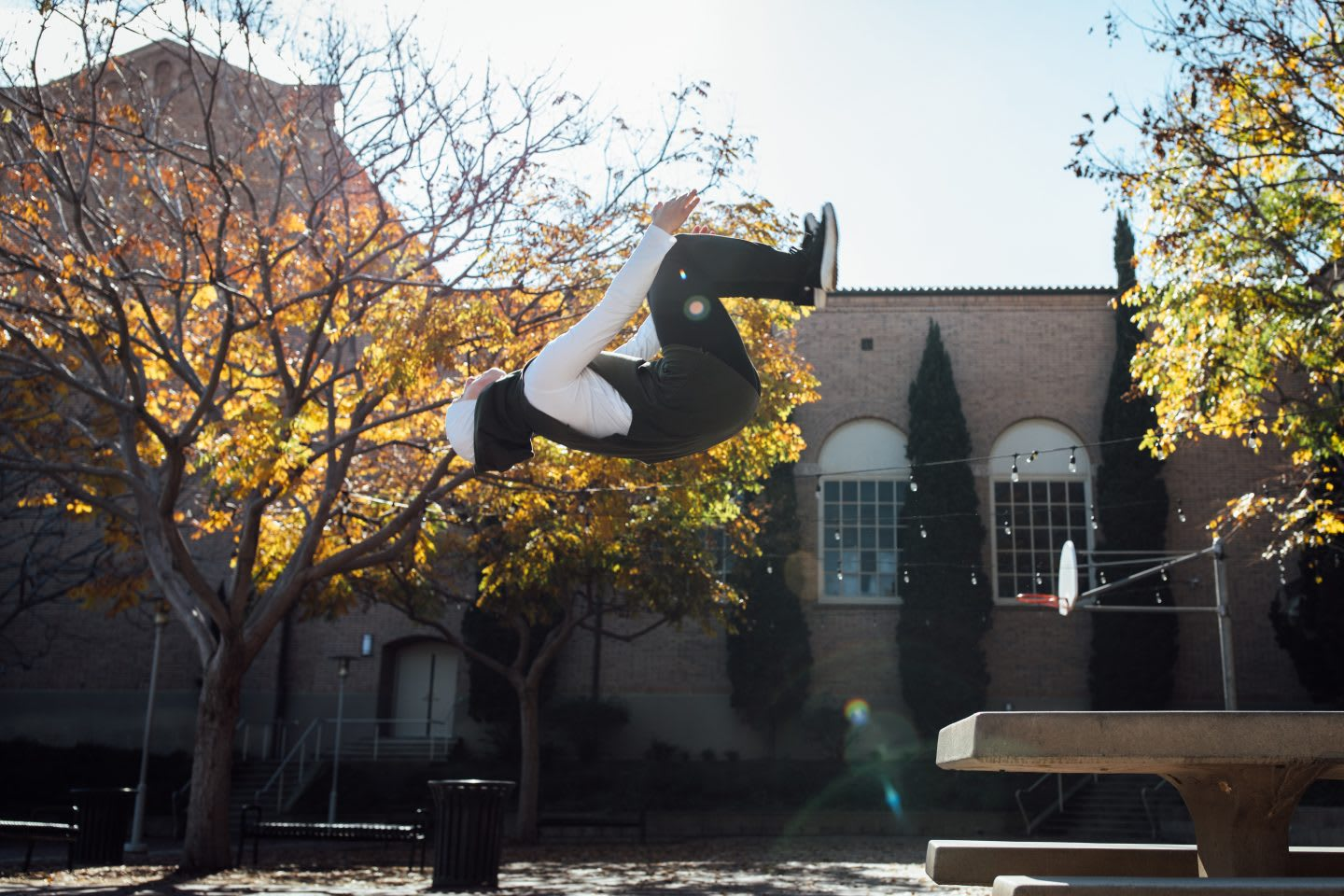 Woman doing backflip in the air on a sunny day, parkour, action, sports, active, athlete, Sara Mudallal