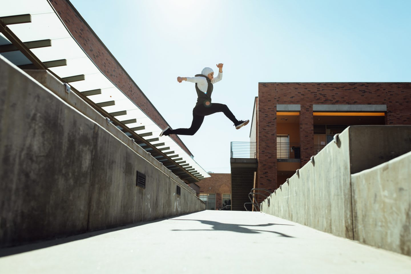 Woman jumping over a path in the sun, parkour, jump, leap, action, sports, exercise, Sara Mudallal, athlete