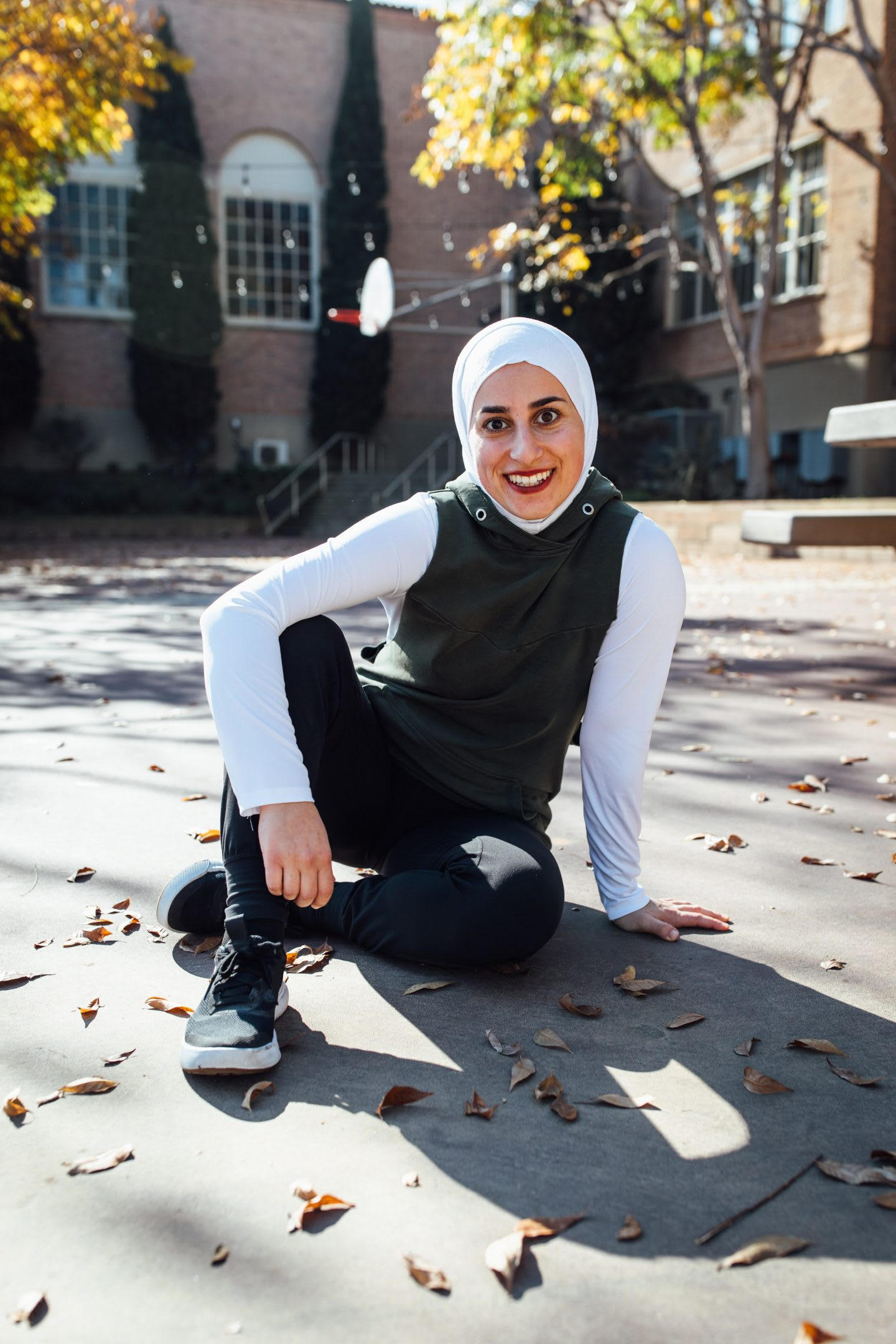 Girl sitting on the ground smiling, parkour, athlete, sports, action, fitness, Sara Mudallal