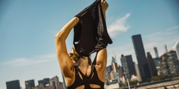 Woman in sports outfit taking off her t-shirt after exercising, sports. workout, city, fitness, adidas