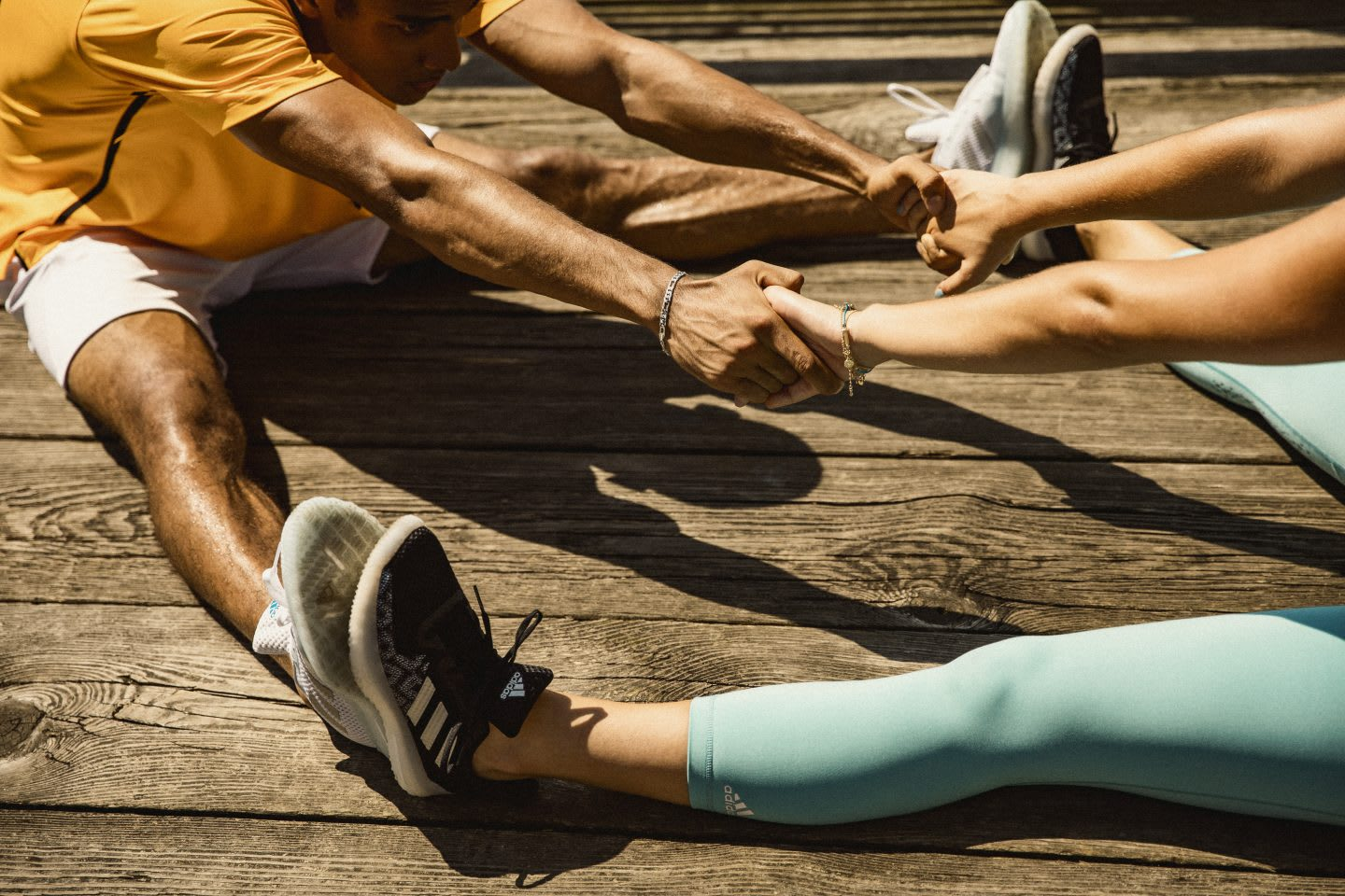 Two people holding hands and stretching after exercising, workout, sport, sport attire, adidas, warmup
