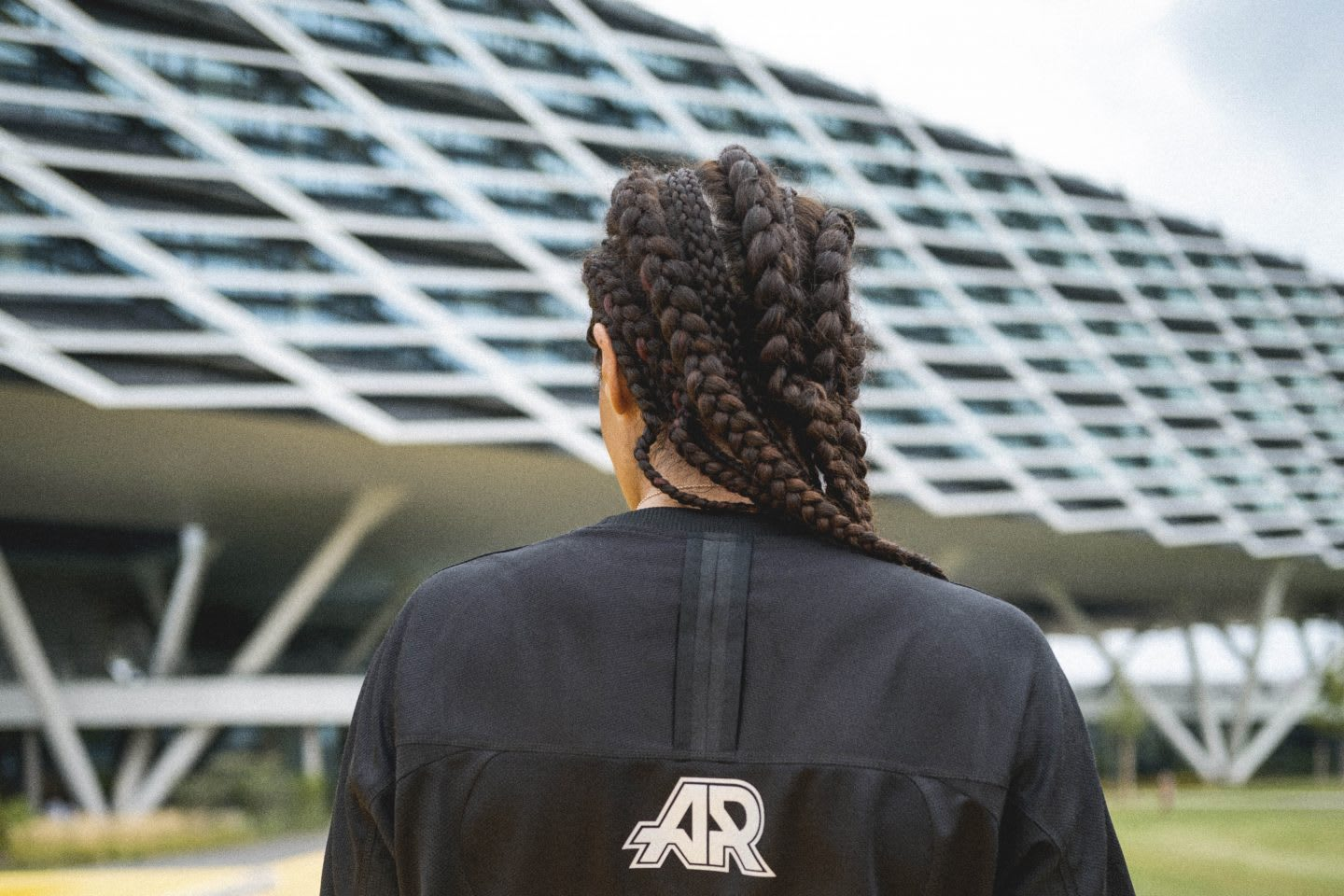 Girl wearing adidas Runners t-shirt staring at the adidas Arena building at the adidas HQ in Herzogenaurach, Germany, culture and workplace, office, campus