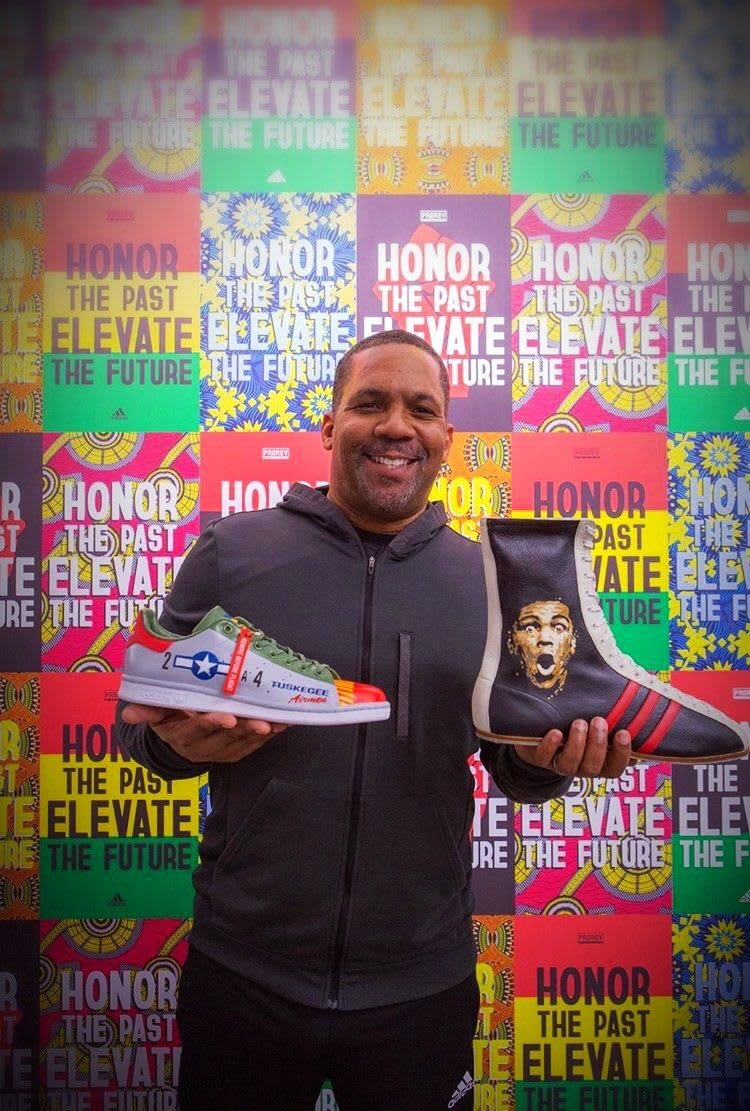 Man holding sports shoes in front of a colorful wall and smiling, sneaks, posters, colors, Todd Stansbury, adidas, employee