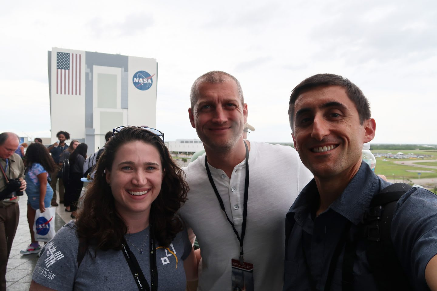 Two men and one woman standing together smiling in a group at NASA, spaces, ISS, sports, collaboration, teamwork, adidas, Nanorocks