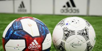 Two adidas soccer balls on an adidas soccer field, blue, red, sports, equipment, exercise