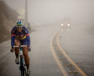 Woman road cycling in the fog on a curving road, cyclist, athlete, growth. mindset