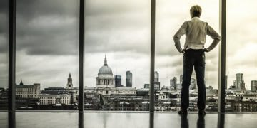 Man staring out of the window at city skyline, thoughtful, growth, mindset, reflection, rejection