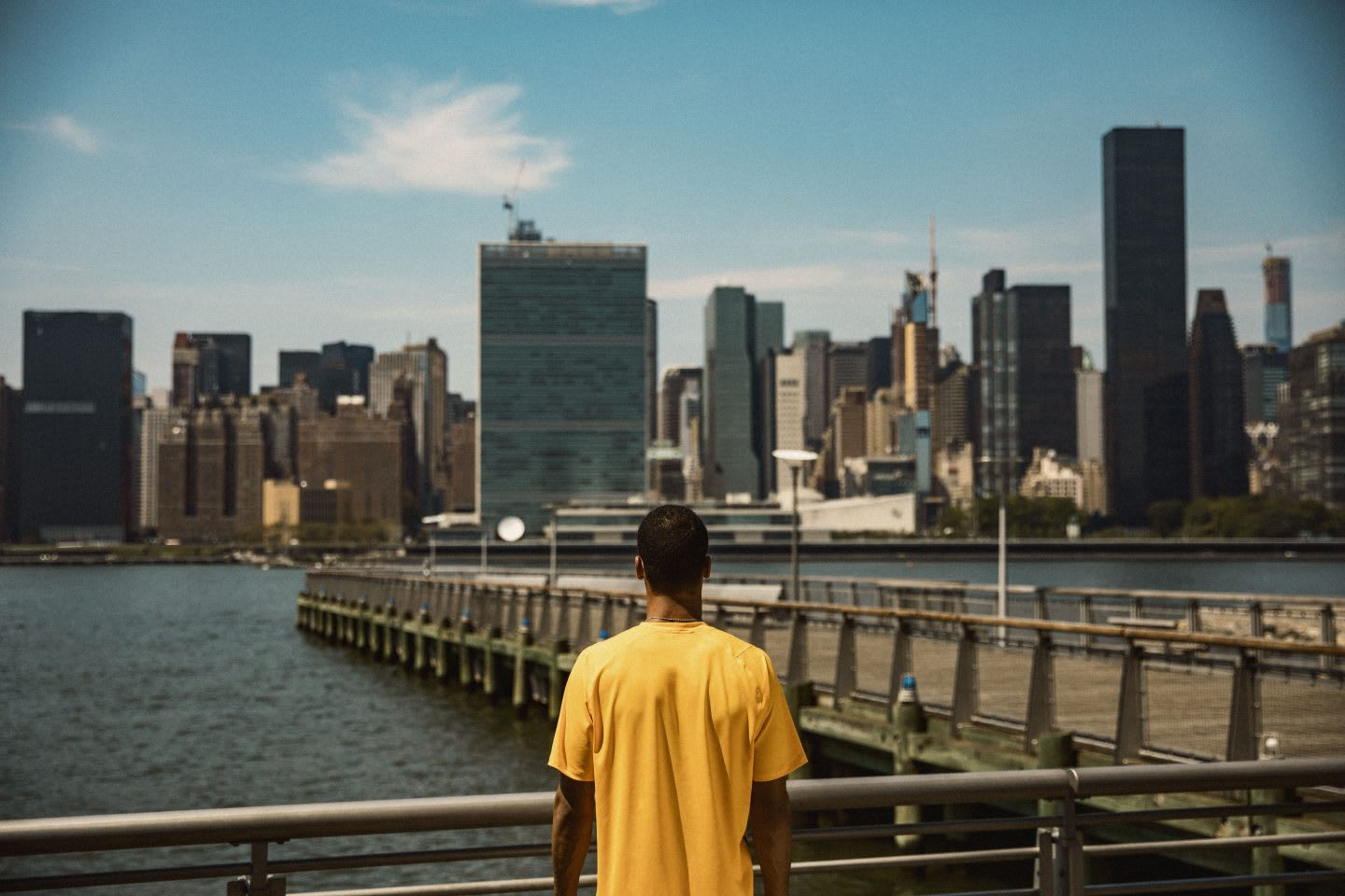 Man wearing a yellow t-shirt looking out at a city skyline, sport, adidas, exercise, fitness, GamePlan A