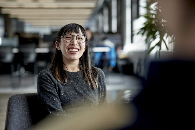 Woman wearing glasses smiling as she is talking to a colleague at work, employee, happy, culture, girl, adidas
