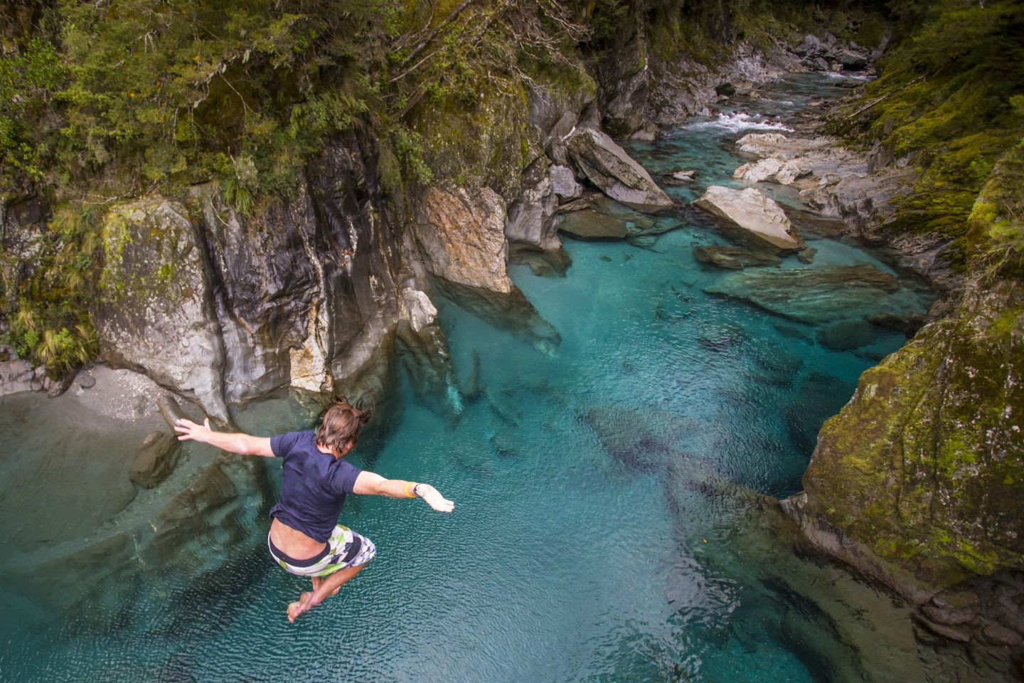 The Blue Pools of Makarora offer enticing blue waters to swim in. A man jumps off a bridge into the water, risk, unknown, leaping, confidence, GamePlan A