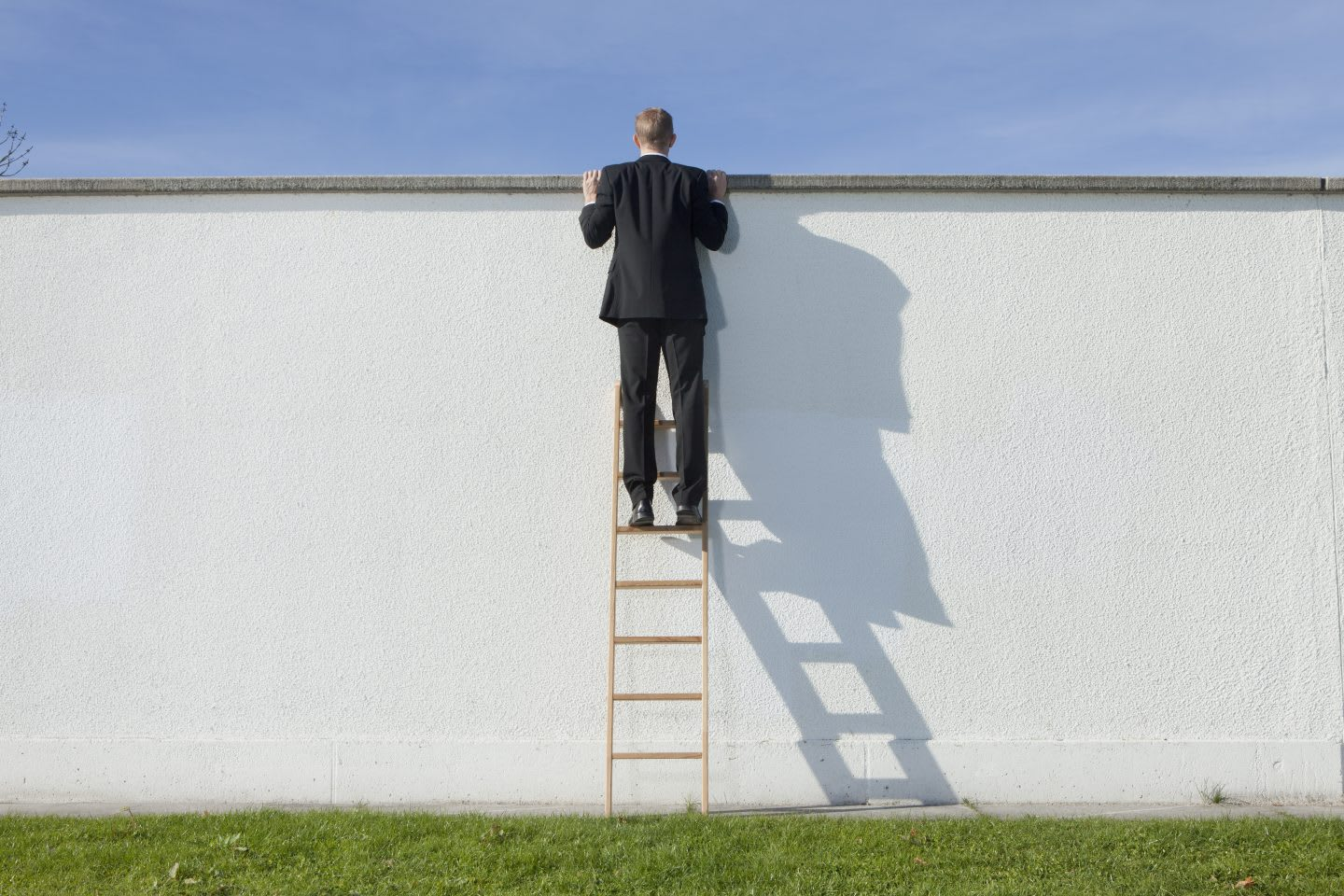 Businessman on ladder looking over wall, curiosity, confidence, unknown, risk, bravery