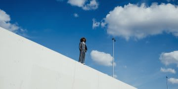 Cool, well-dressed young man with afro standing on sunny urban wall, leap, jump, high, unknown, GamePlan A
