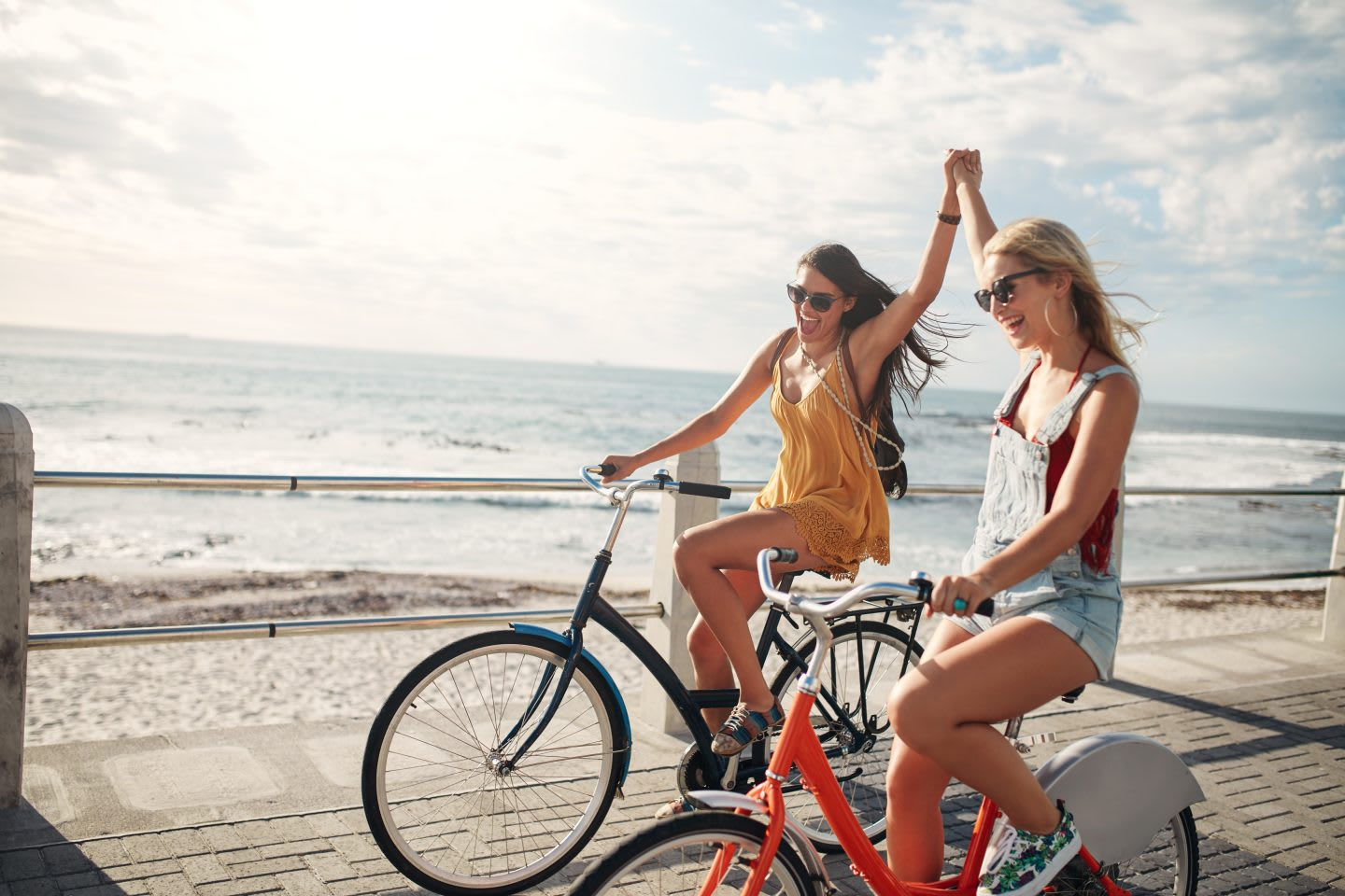 Female friends enjoying cycling on a summer day. Two young female friends riding their bicycles on the seaside promenade, cycling, biking, cyclists, fun