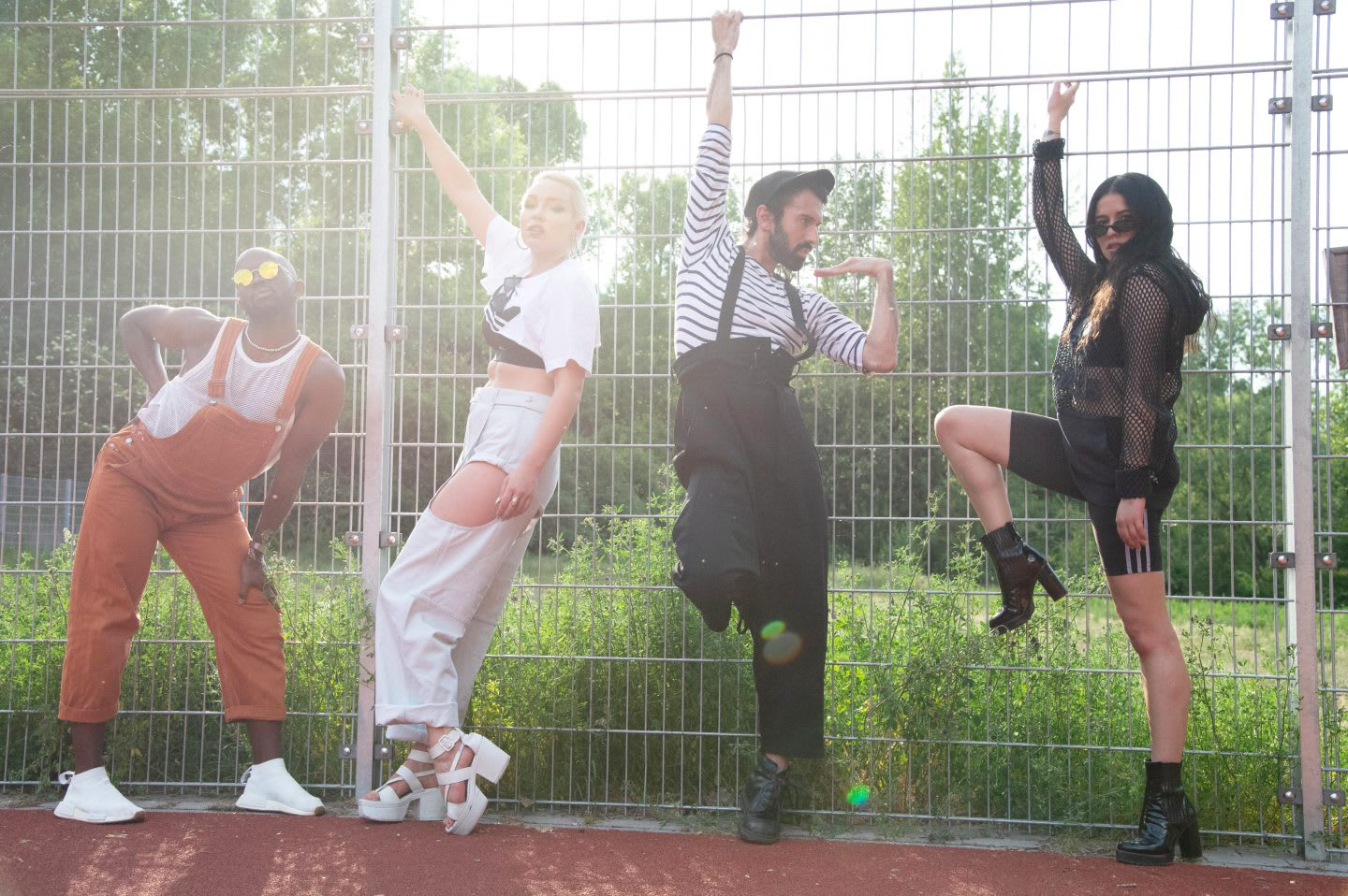 Two men and women posing dramatically against a wire fence, voguing, vogue, photography, attitude, posing, adidas, employees, confidence, GamePlan A