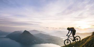 Mountain biker descends steep mountain slope above lake, mountain, biking. bike. view, cycling