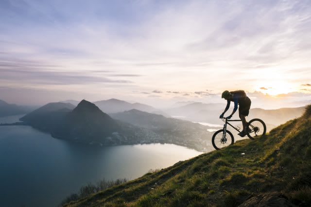 Mountain biker descends steep mountain slope above lake, mountain, biking. bike. view, cycling