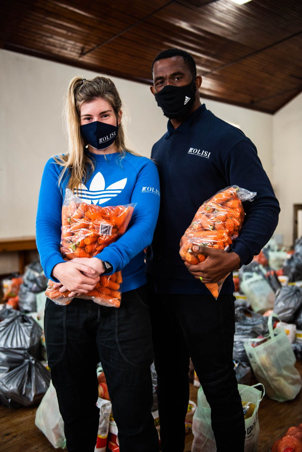 Rachel and Siya Kolisi holding bags of carrots for communities in South Africa during coronarvirus pandemic, volunteering, donation, help. South Africa, Kolisi Foundation