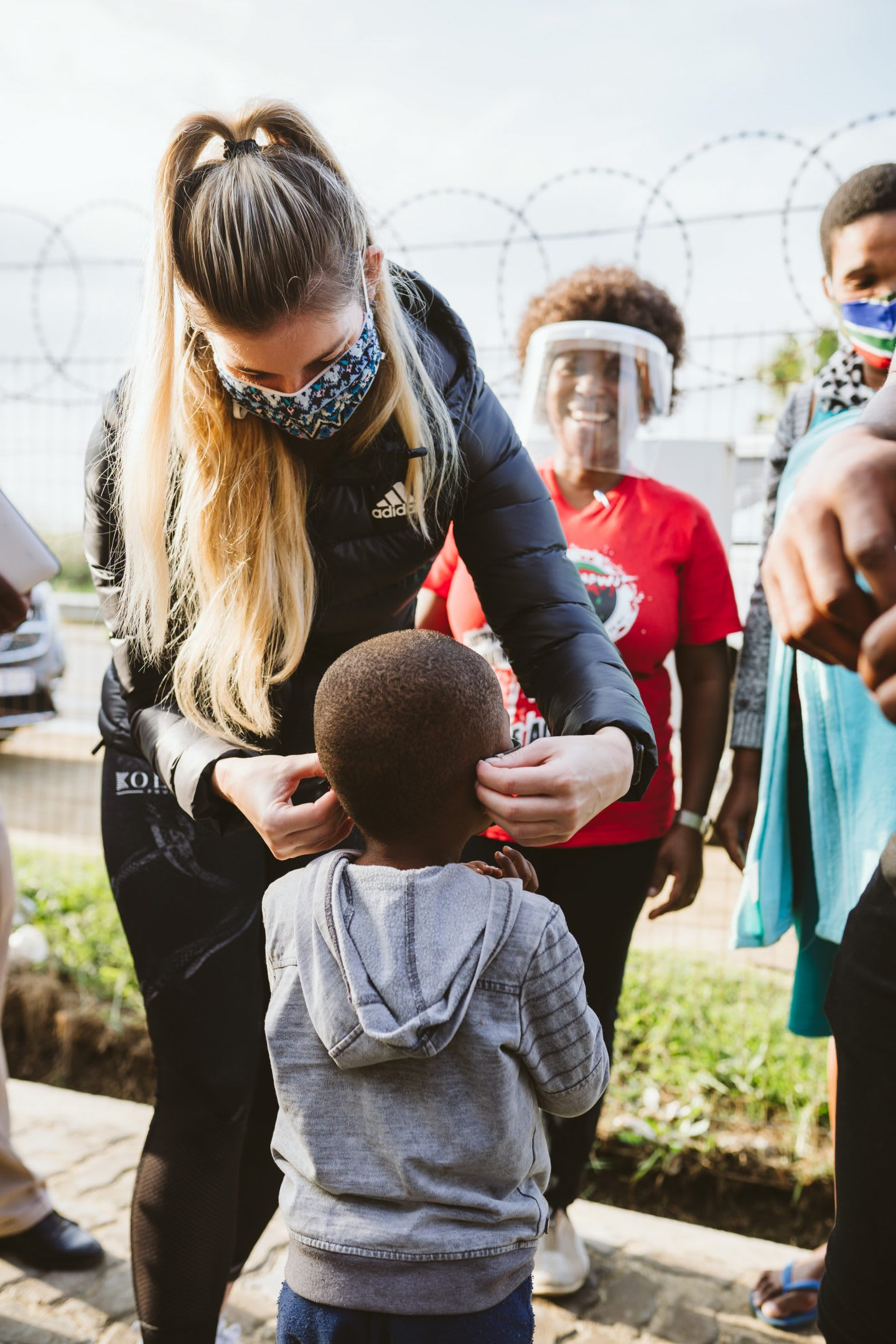 Rachel Kolisi putting a mask on a child in South Africa during coronavirus pandemic, volunteering, help. donation, Kolisi Foundation, South Africa
