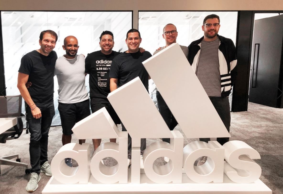 adidas employee Mo Adlouni stands with his teammates behind the adidas sign, workplace, career, work, team, culture, adidas
