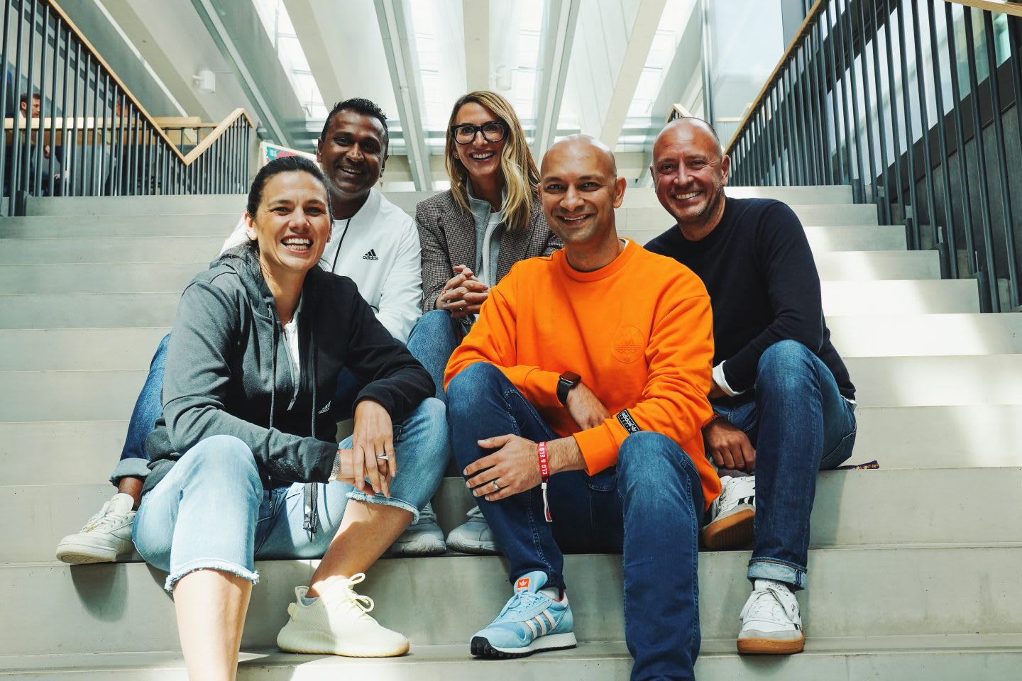 A team of diverse men and women sitting on steps smiling, teamwork, diversity, workplace, culture, colleagues, adidas