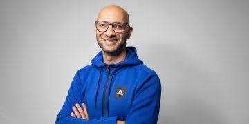 Man wearing blue adidas sweatshirt and glasses crossing arms and smiling, Alim Dhanji SVP HR Talent and Global Brands, adidas, employee, culture, workplace, GamePlan A