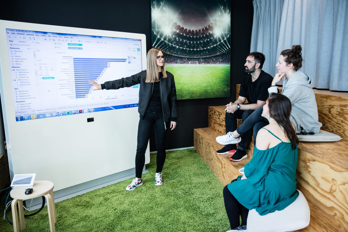 Girl presenting data on a screen to teammate during work meeting, adidas, digital, technology, data, workplace, teamwork