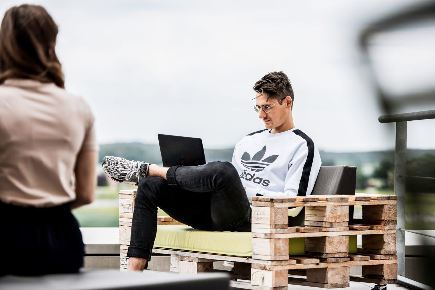 Man working on his laptop in an outdoor working space. adidas, working, workspace, digital, technology