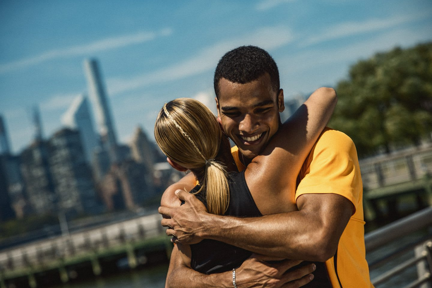 Man wearing yellow t-shirt smiling while hugging a blonde woman, teamwork. support, friendship, happiness, sports, sportsmanship, adidas