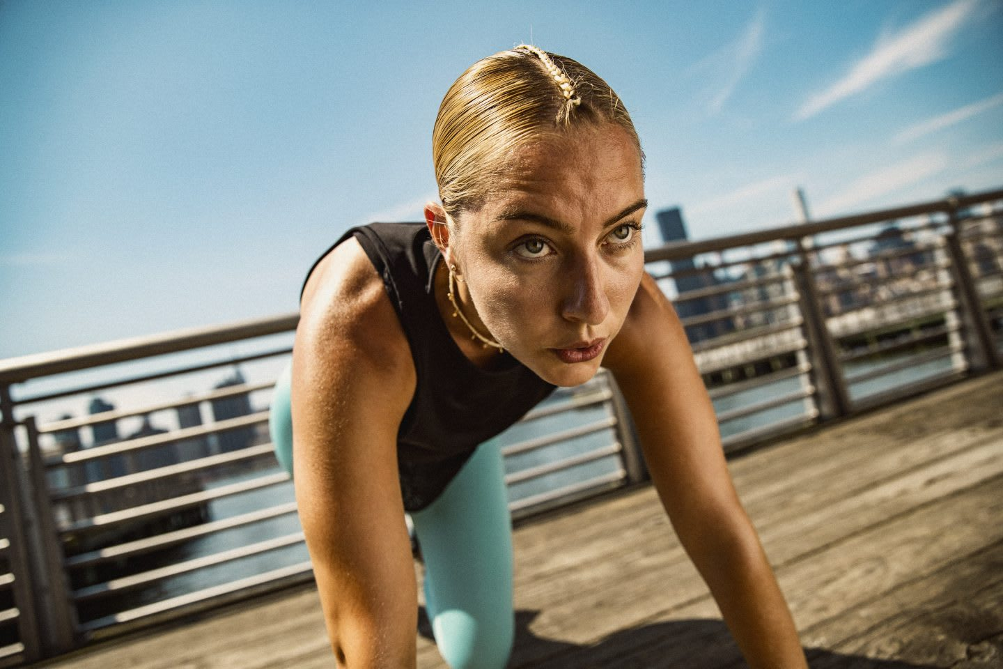 Woman looking focused and determined while doing sports on a boardwalk near a city, skyline, active, sport, lifestyle, mindset, adidas, female, athlete