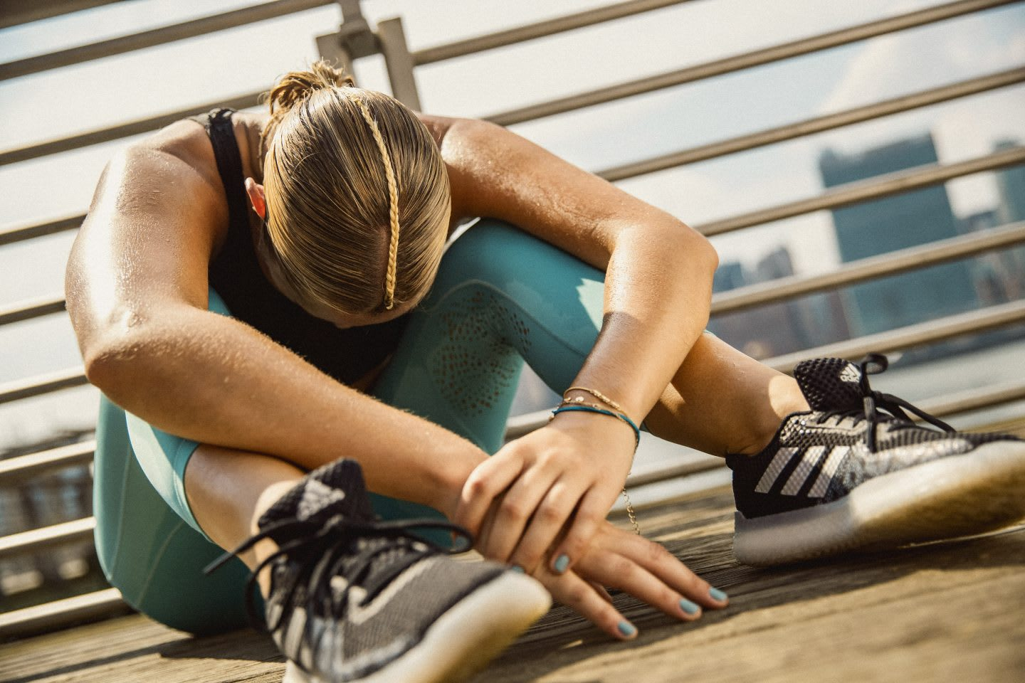 Woman wearing adidas shoes and adidas apparel sitting with head between legs resting and recovering after sports, tired, active, sport, lifestyle, mindset, GamePlan A