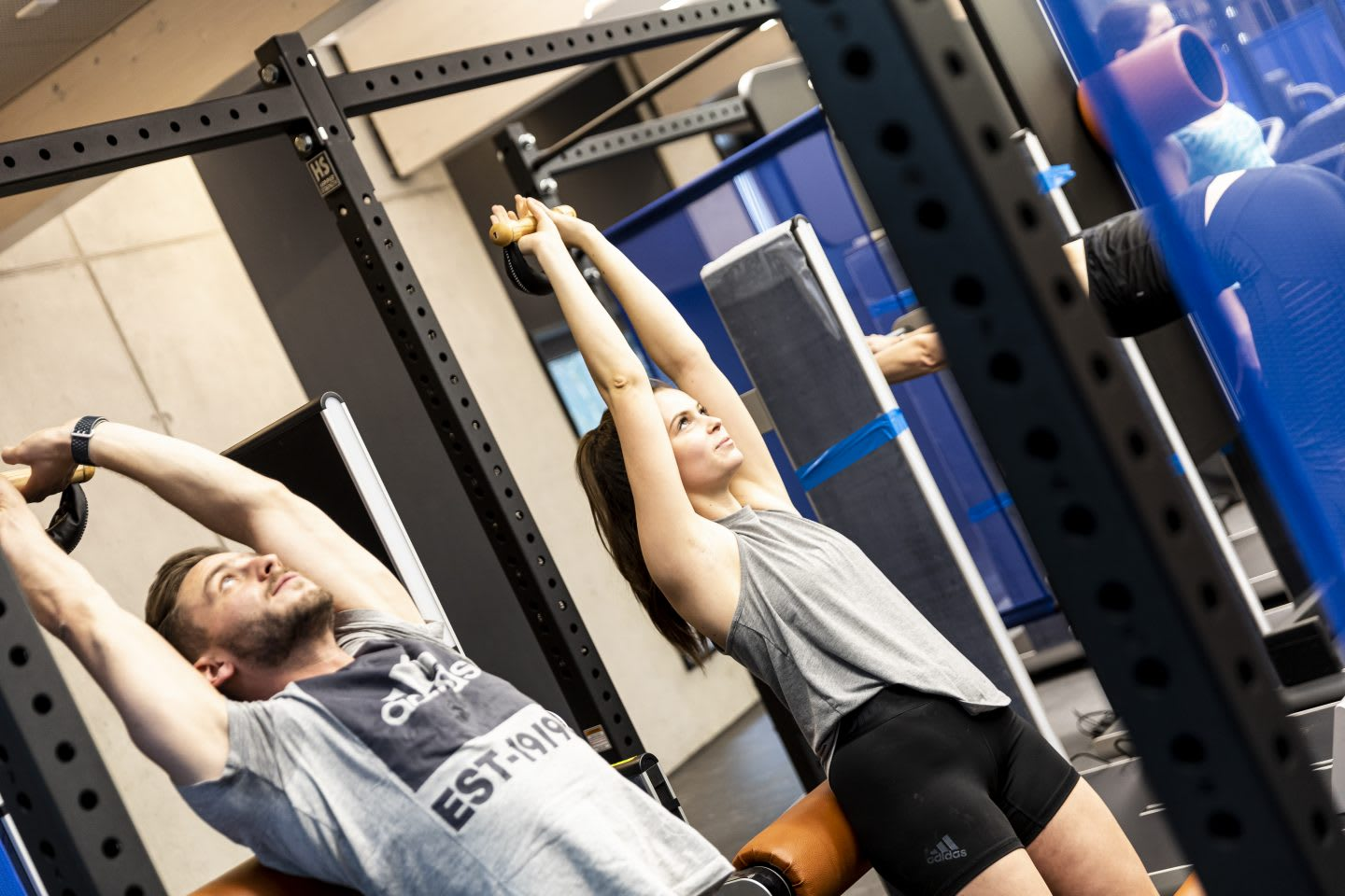 Man and woman using workout equipment while exercising during a workout class at a gym, GYM, Herzogenaurach, adidas, employees, workplace, fitness. sports, culture, active, health, lifestyle