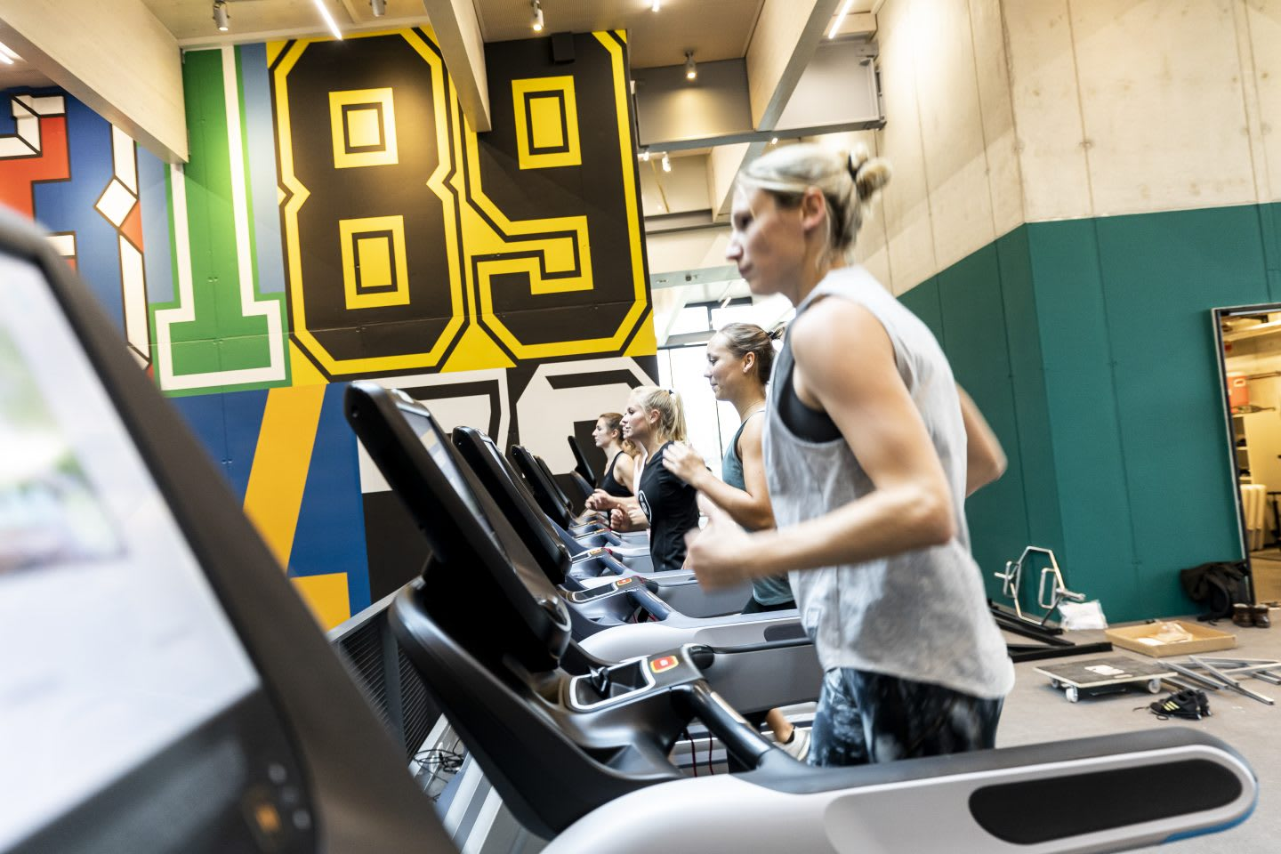 Woman wearing tanktop running on treadmill at a gym, GYM, Herzogenaurach, adidas, employees, workplace, fitness. sports, culture, active, health, lifestyle