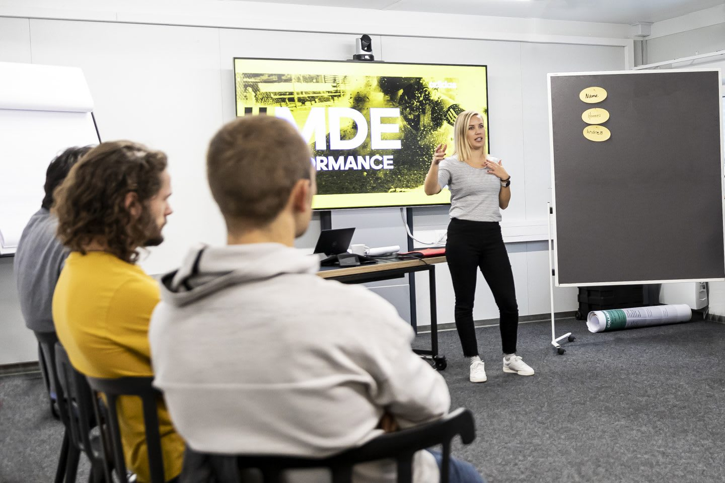 Group of employees sitting in a circle listening to a woman present during a workshop, adidas, leadership, seminar, MDE, DDE