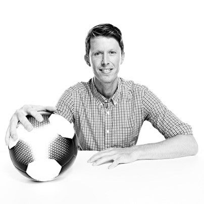 Man wearing a checked shirt posing with football in right hand, James Bean, adidas, employee