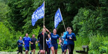 A group of people wearing blue carrying blue flags running as a team through a park, Run for the Oceans, RFTO, running, sports, fitness, Sarah Sanderson, adidas, employee, sport, purpose, oceans, sustainability