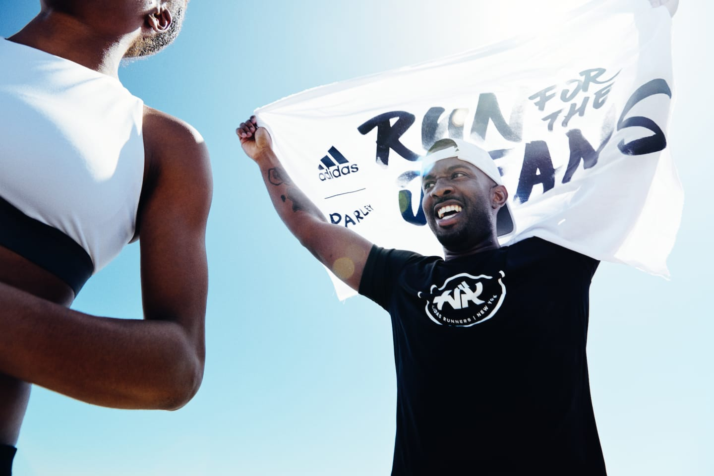 Man wearing black t-shirt holding up white flag in black lettering, Run for the Oceans, running, runners, event, sport, purpose, sustainability, adidas