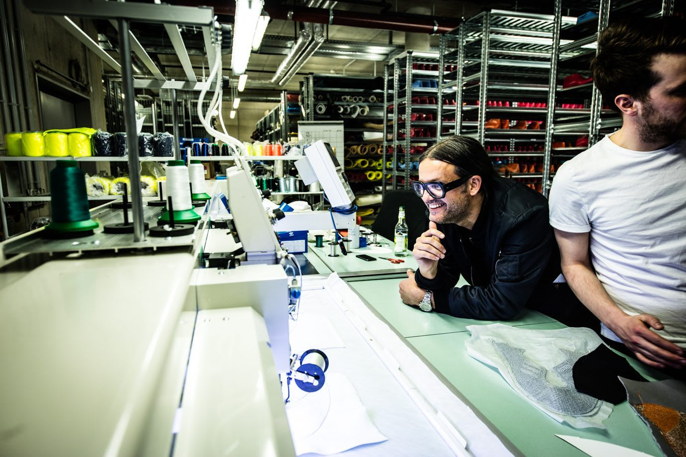 Man wearing black framed glasses smiling and looking at materials, teamwork, sustainability, Parley for the Oceans