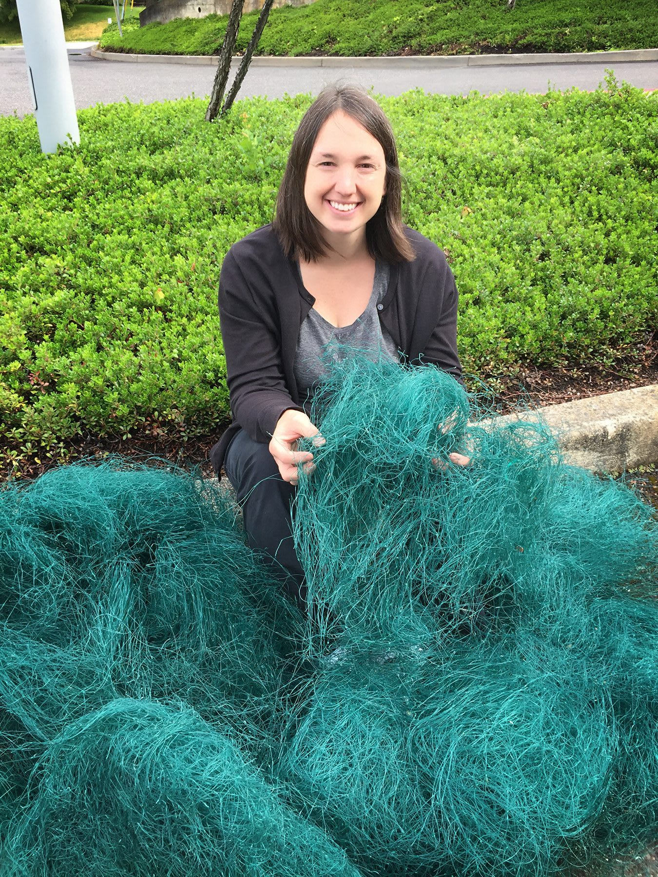 Woman holding green net and smiling, Kelli George, adidas, employee, plastic waste, materials, innovation