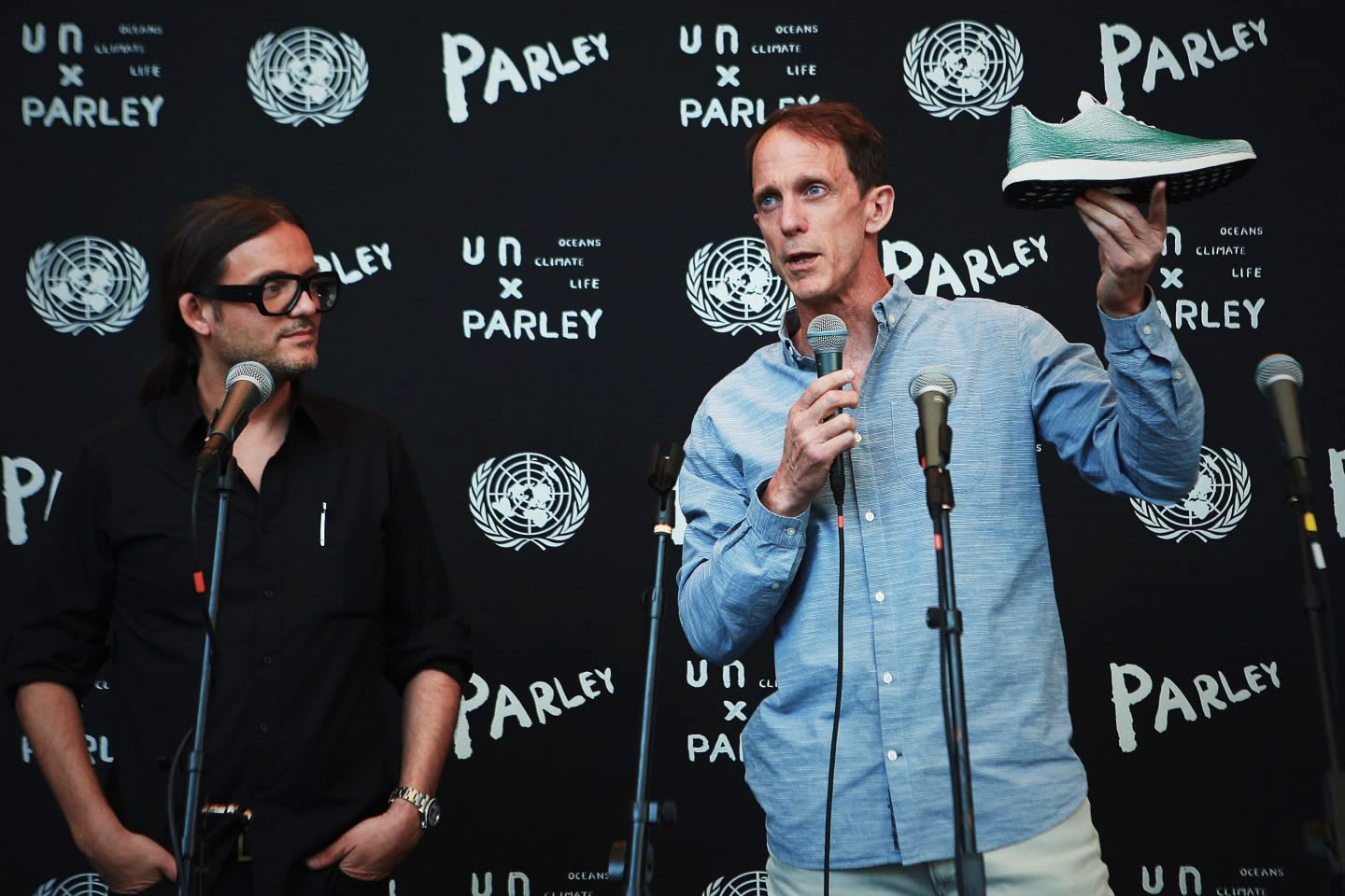 Man wearing blue shirt holding up a sneaker while giving a speech on stage, Eric Liedtke, Cyrill Gutsch, CEO, founder, Parley for the Oceans, United Nations, sustainability