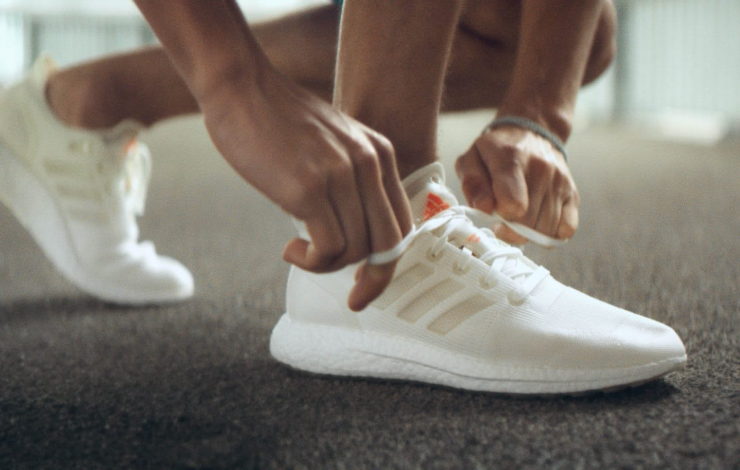 Person tying shoe laces on white sneakers before starting a run, FUTURECRAFT, LOOP, recycle, sustainability, remade