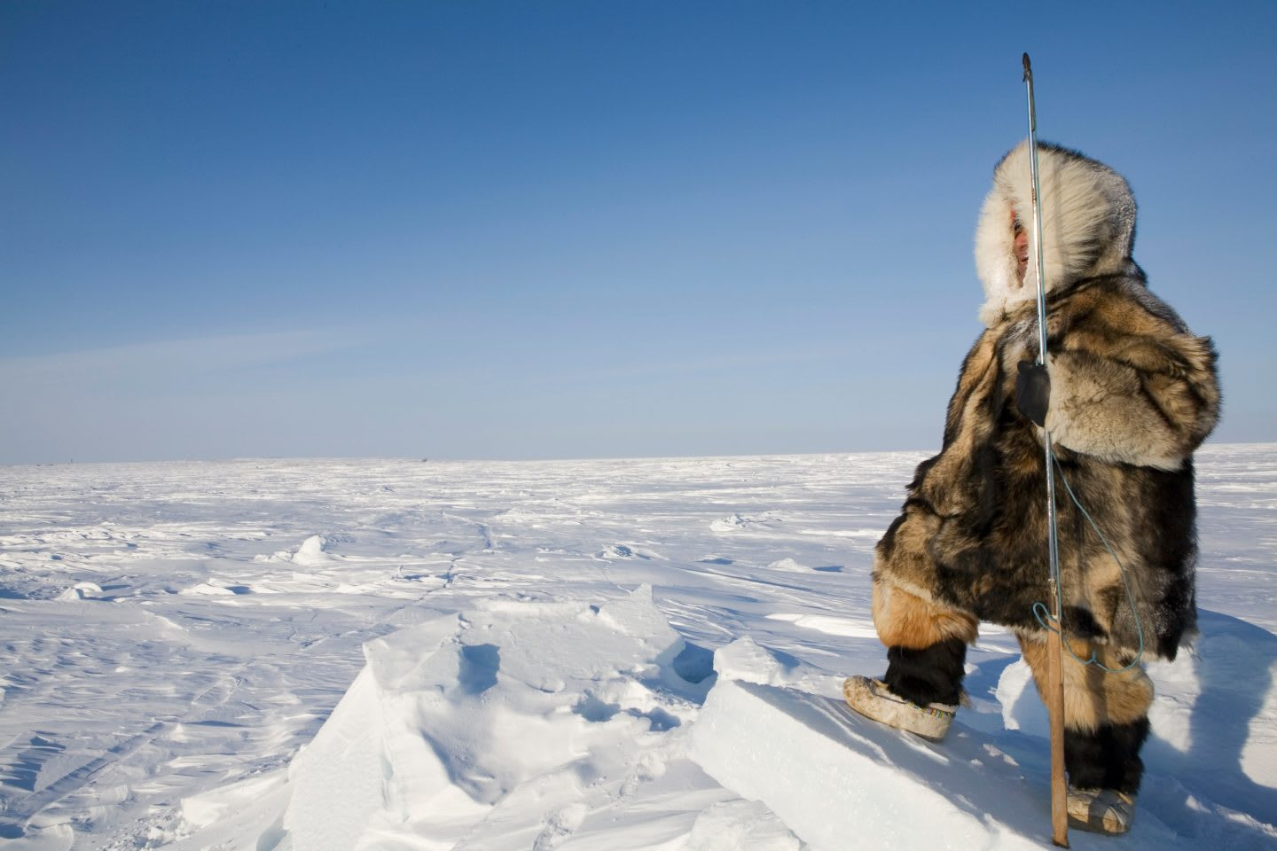 An Inuit man is hunting for wild animals on the north pole, Canada, cold, outdoor, anorak