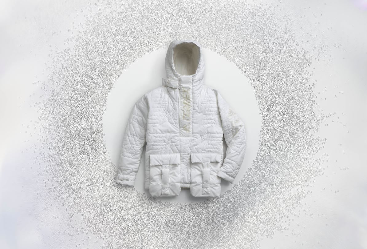White winter jacket on white background surrounded by small pellets, FUTURECRAFT, LOOP, Anorak, ISPO, sustainability, fashion, adidas